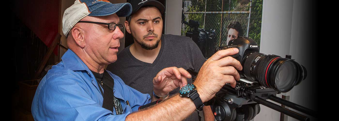 A NYFA AU student with a goatee concentrates as his instructor explains a technique for the Canon camera.
