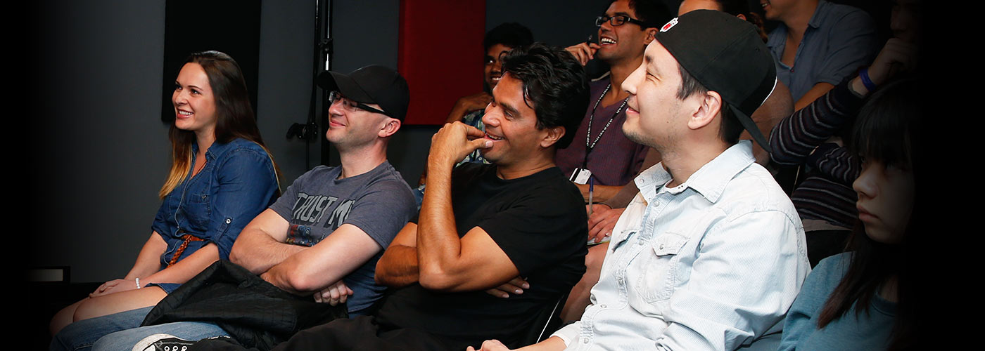 A diverse group of NYFA AU students sit in a theatre smile as they engage during a lecture.