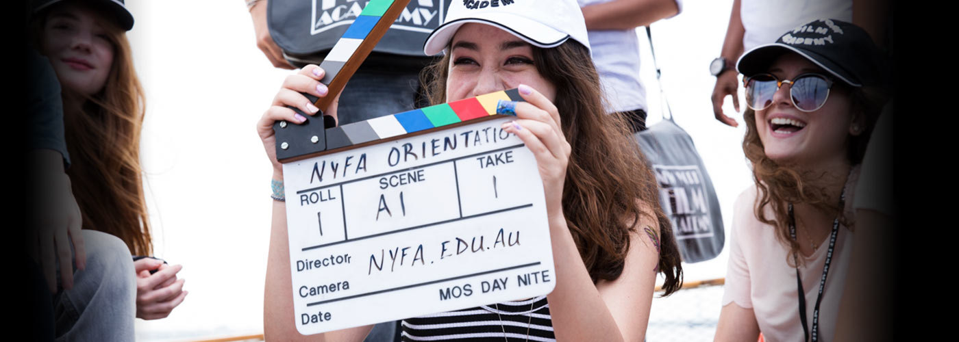 A NYFA AU student smiles from behind a slate as she and her classmates prepare for a take.