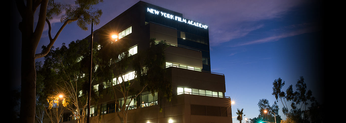 The NYFA LA building is seen lit at night under a pink and blue California sky during the LA Study Tour.