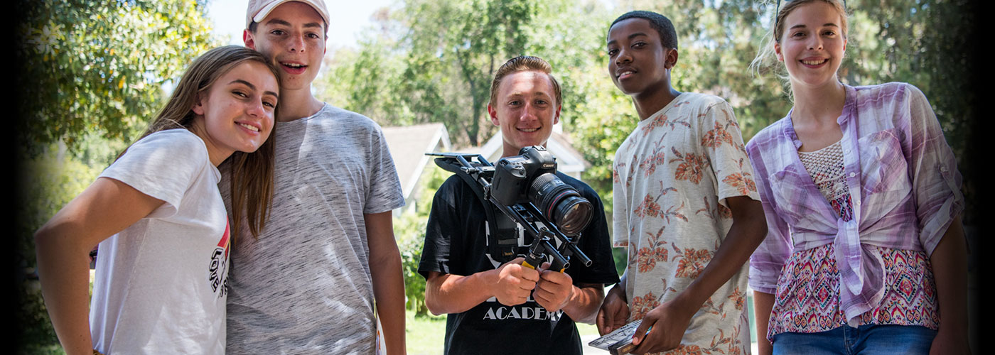 Five smiling NYFA summer camp students pose while one holds a shoulder mounted camera
