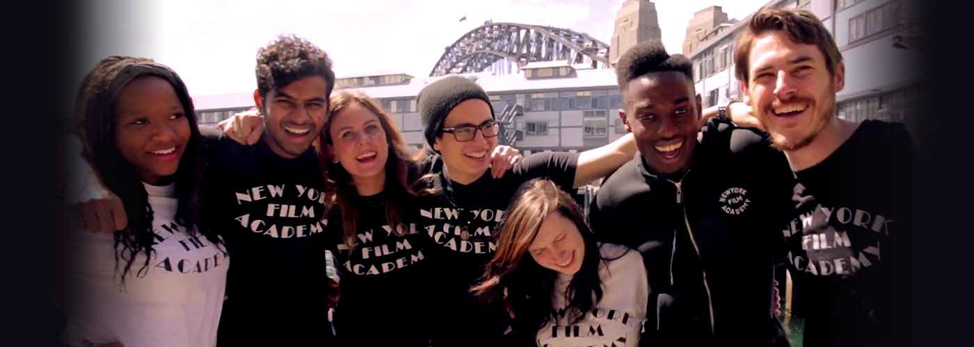 A diverse group of smiling students in black and white New York Film Academy t-shirts pose together outside the New York Film Academy Australia's Sydney campus location.