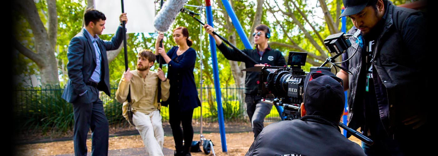 Three NYFA AU filmmaking students talk by a swingset while being filmed by a RED Camera.