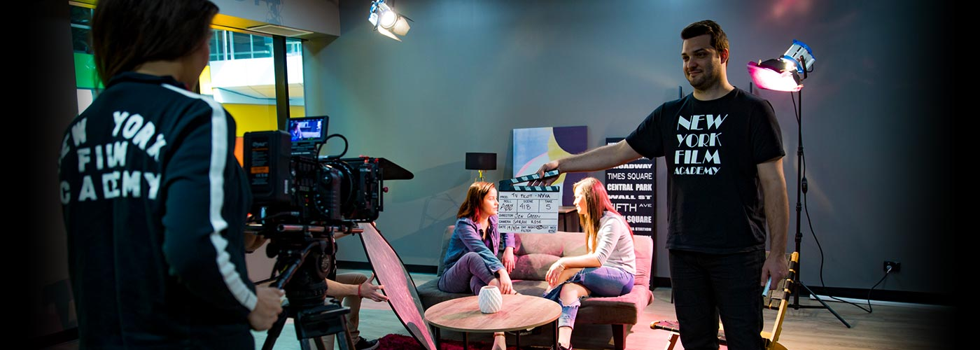 A scene of two girls talking on a couch being filmed on a NYFA set