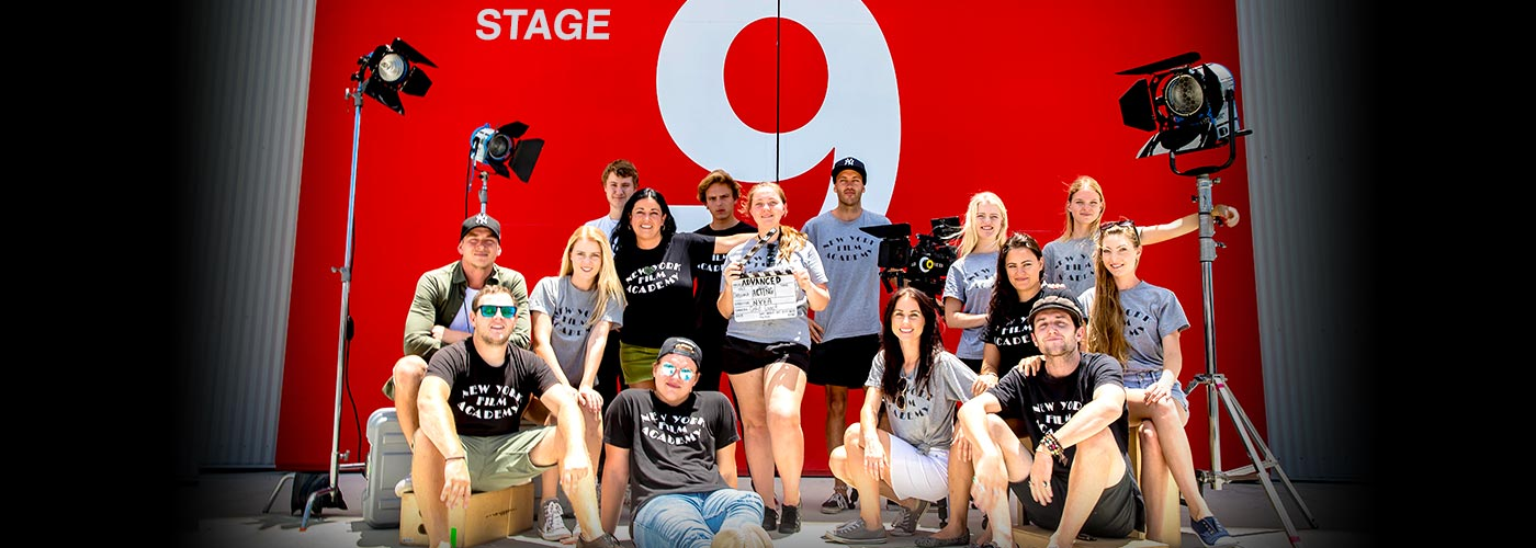 A group of NYFA Australia students smiling in front of a red wall outside