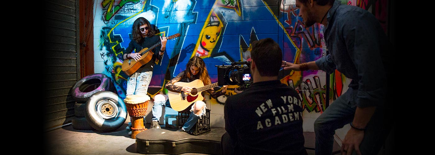 Two NYFA Australia students are filmed playing guitar near a graffitied wall